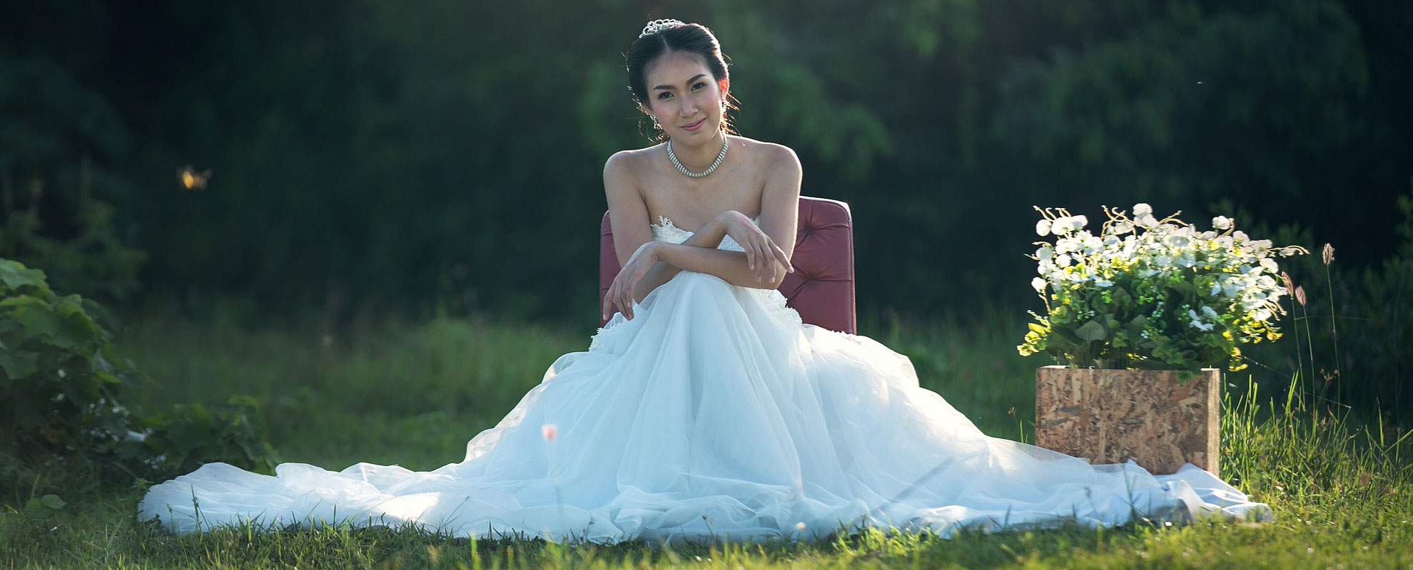 a young bride in a wedding dress sitting outside in a green field